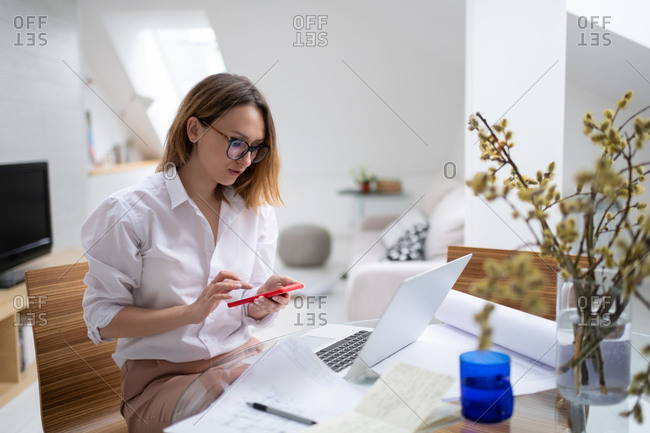 Busy woman working at home and using smartphone