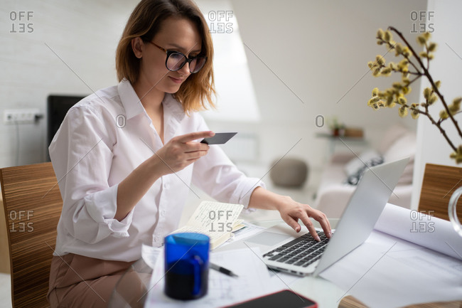 Busy woman doing online purchase on laptop