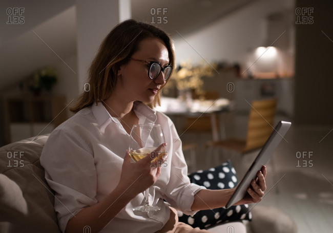 Young woman with glass of wine using tablet at home