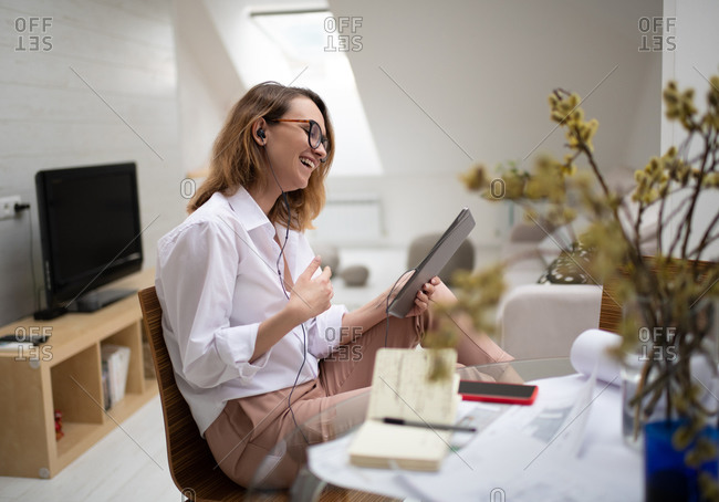 Delighted young businesswoman enjoying video chat with colleagues