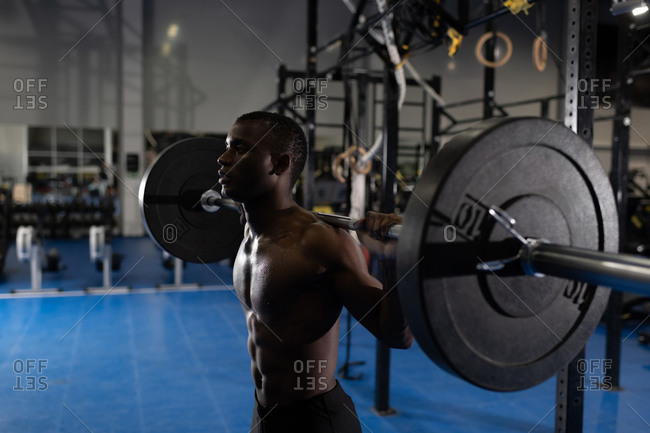 Young African American athlete exercising with barbell