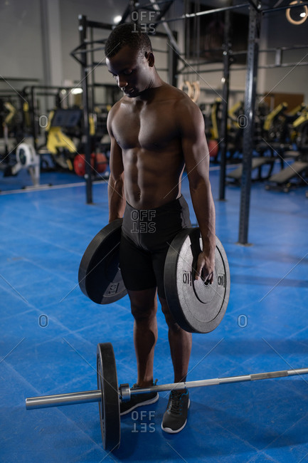 Sportive muscular man standing next to barbell and holding plates