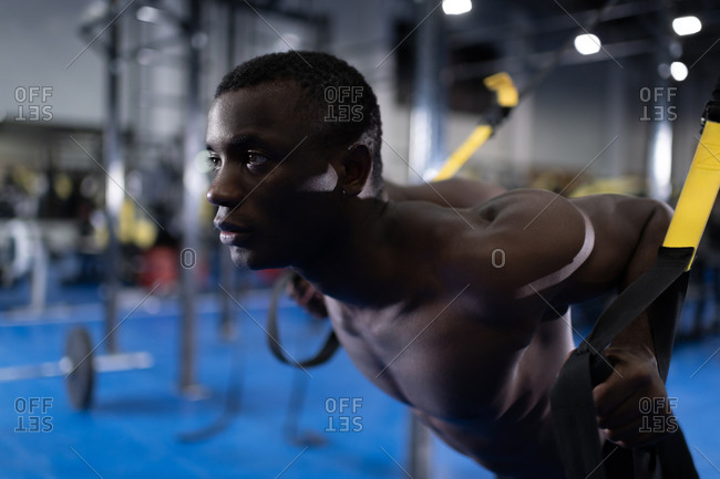 African American man training with trx equipment in gym