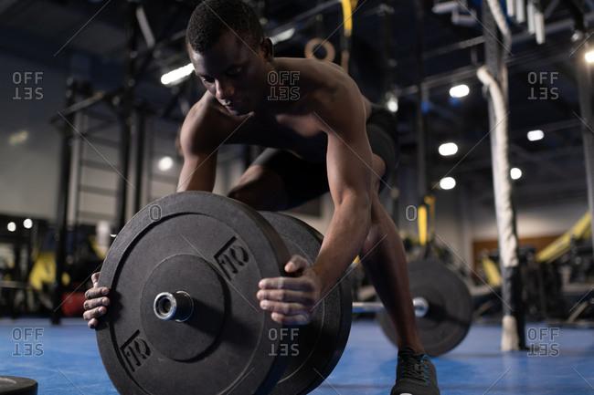 African American sportsman preparing barbell for exercising