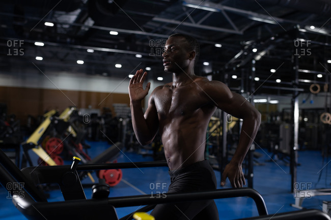 Sportive black man exercising on treadmill in fitness club