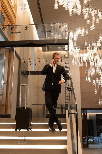 Businessman talking on smartphone in hotel lobby