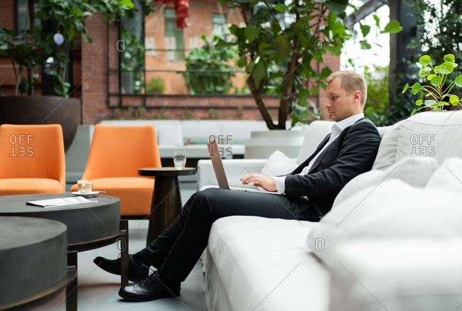 Businessman using laptop on hotel terrace