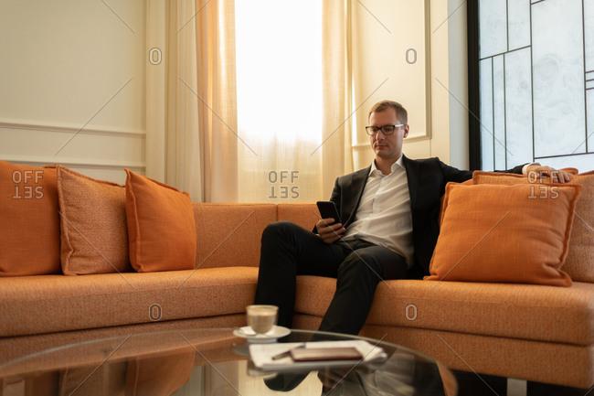 Modern businessman surfing internet on smartphone in hotel