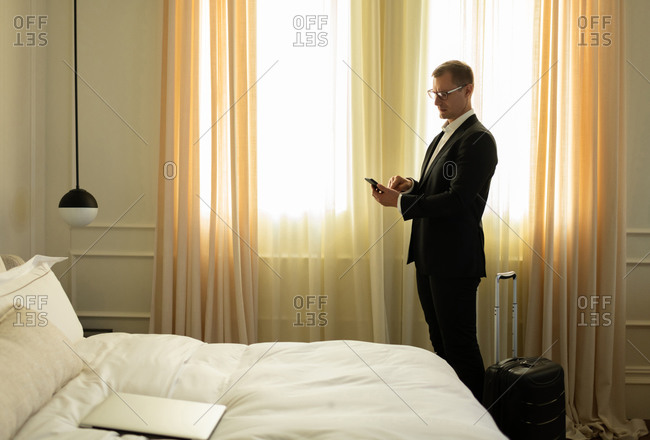 Adult businessman using smartphone after arriving in hotel
