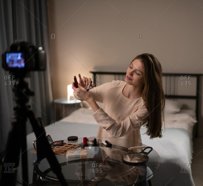 Young beauty blogger trying lipstick in front of camera