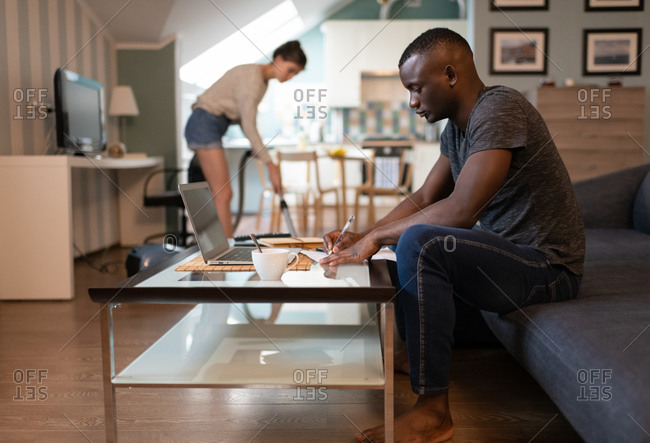 Black man working remotely at home with girlfriend cleaning room