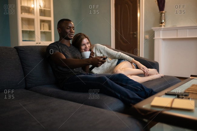 Diverse couple cuddling on sofa and watching tv together