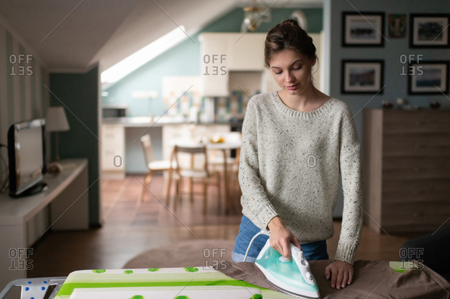 Young lady ironing clothes carefully