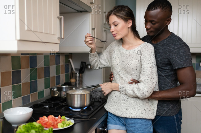 Diverse couple cooking in modern kitchen