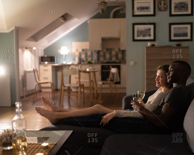 Diverse couple relaxing on sofa with wine in evening