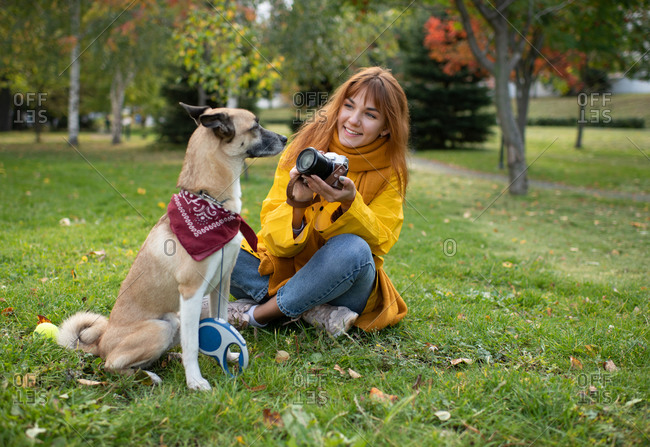 Smiling lady shooting cute dog in park