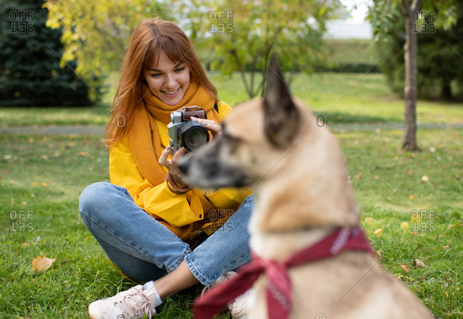 Cheerful woman photographing blurred dog in park