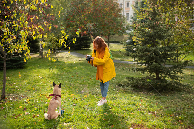 Young lady taking pictures of dog on grass