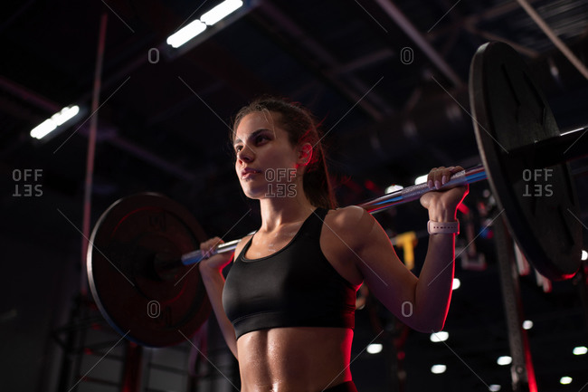 Powerful woman lifting barbell during functional training