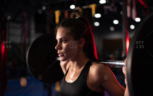 Sweaty woman exercising with barbell in gym