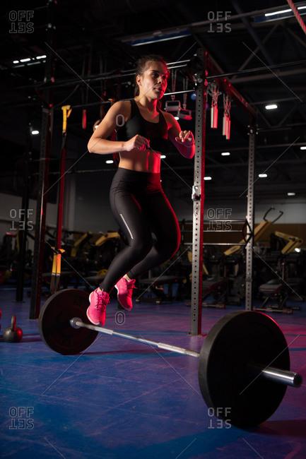 Slim sportswoman jumping over barbell