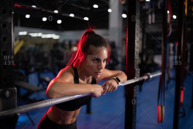 Powerful sportswoman leaning on weightlifting bar