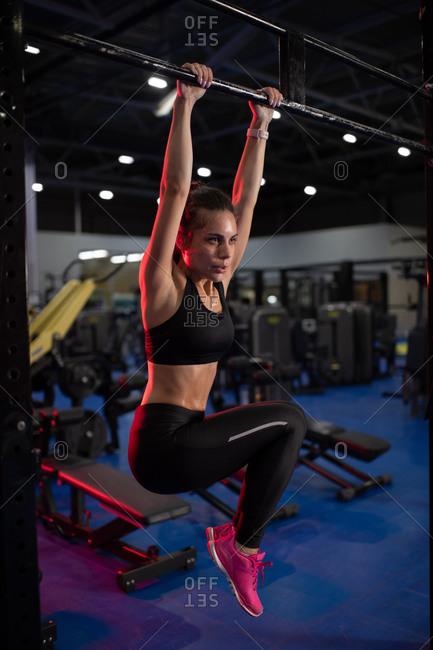 Slim sportswoman doing abs exercise on bar