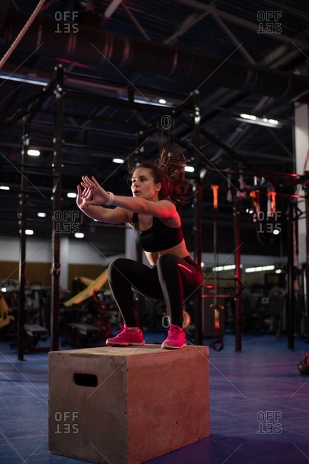 Strong woman jumping on gym box during workout
