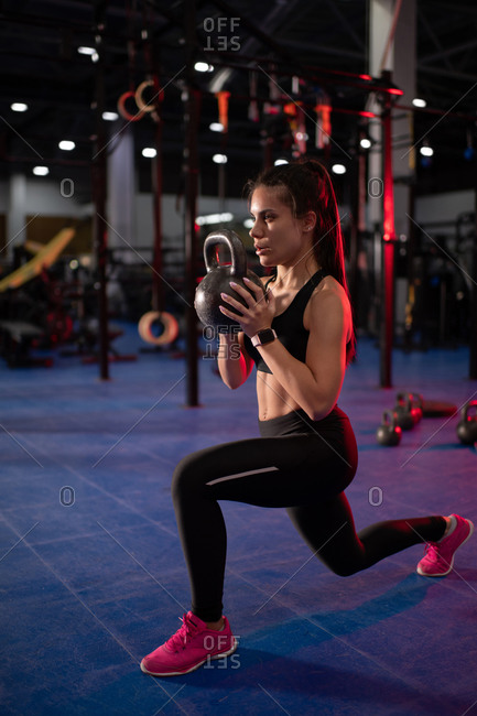 Muscular sportswoman lunging with kettlebell