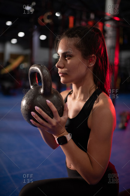 Strong lady exercising with kettlebell in contemporary gym
