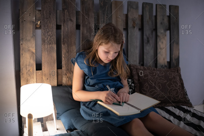 Girl drawing in notepad on bed