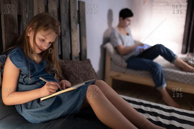 Girl doing homework near working mother