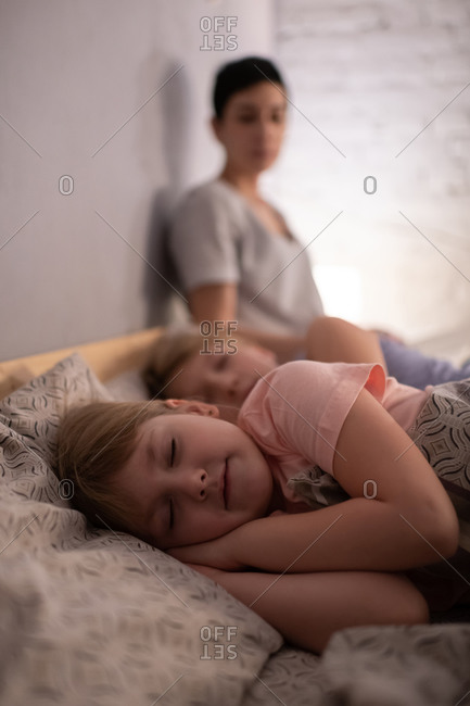 Girl sleeping on bed near sister and mother