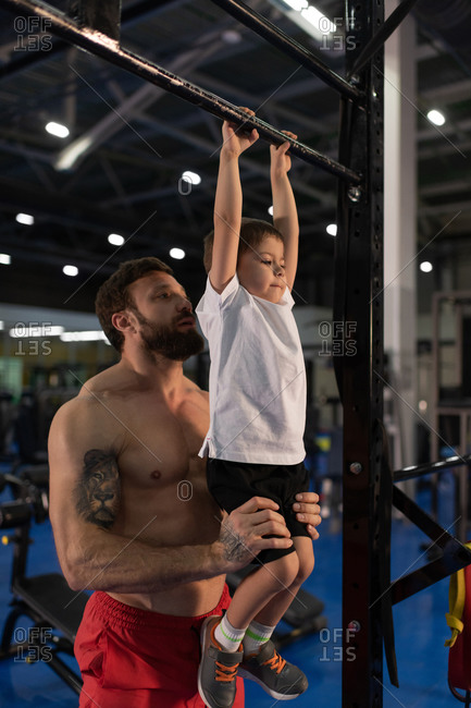 Bearded father teaching son to do pull ups