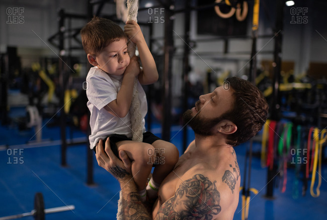 Bearded father pushing son during climbing rope lesson