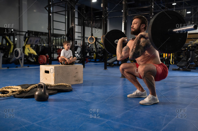 Son supporting father during weightlifting training
