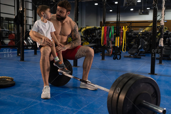 Strong father talking with son during break in training