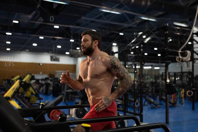 Strong male athlete running on modern treadmill