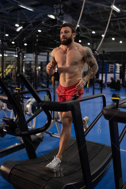 Shirtless athlete running on treadmill during training