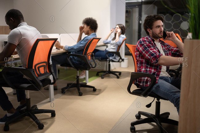 Multiethnic colleagues sitting at desks in coworking space