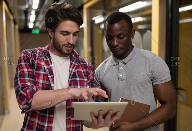 Diverse men using tablet in office corridor
