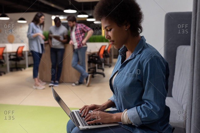 Black woman using laptop in creative workplace