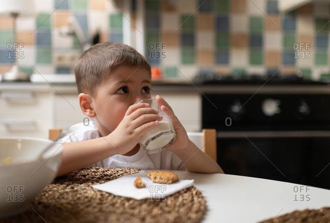 Cute boy drinking milk for breakfast