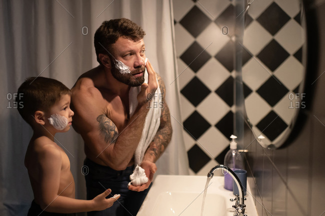 Father showing son how to smear shaving foam