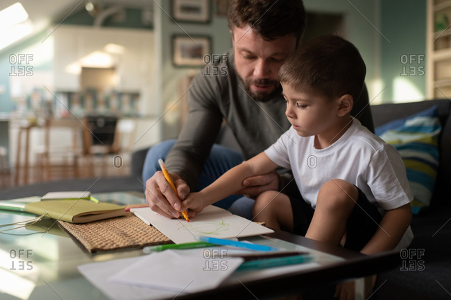 Father drawing with son at home
