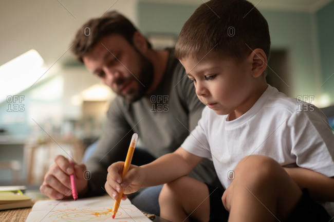 Focused boy drawing with father