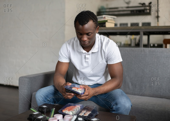 Black man opening containers with sushi at home