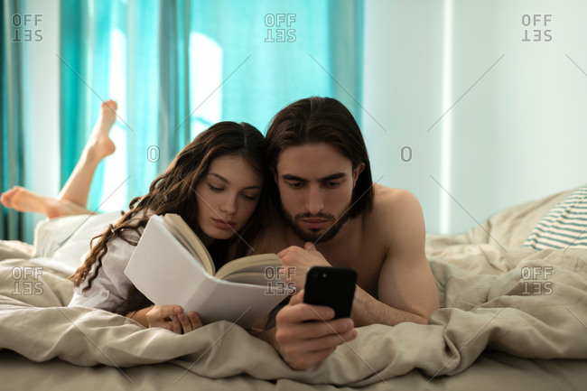 Young man looking at smartphone while his girlfriend reading boo