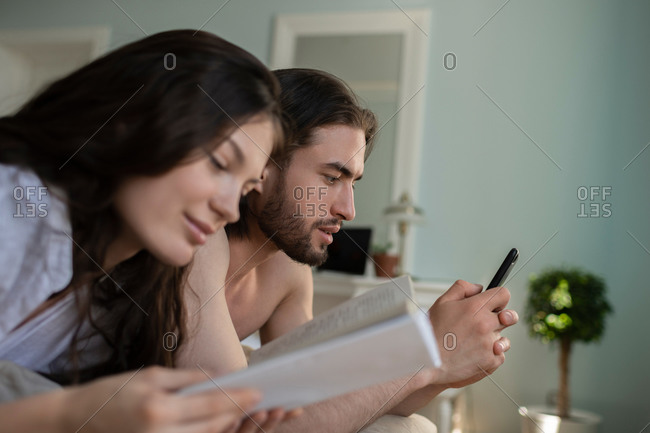 Man watching movie near girlfriend with book
