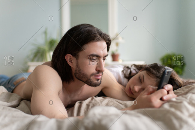 Married couple in bed using mobile phone